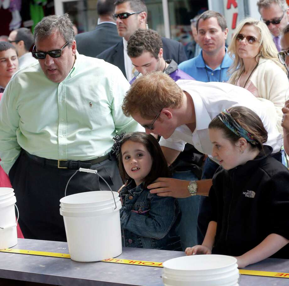 Britain's Prince Harry speaks with Allie Cirigliano, 7, of Middletown, N.J. as they play ball toss together on the Seaside Heights Boardwalk as  N.J. Gov. Chris Christie looks on Tuesday, May 14, 2013 in Seaside Heights, N.J.  Prince Harry began a tour  of New Jersey's storm-damaged coastline, inspecting dune construction, walking past destroyed homes and shaking hands with police and other emergency workers.  New Jersey sustained about $37 billion worth of damage from the storm. Photo: Andrew Mills, AP / The Star-Ledger, Pool