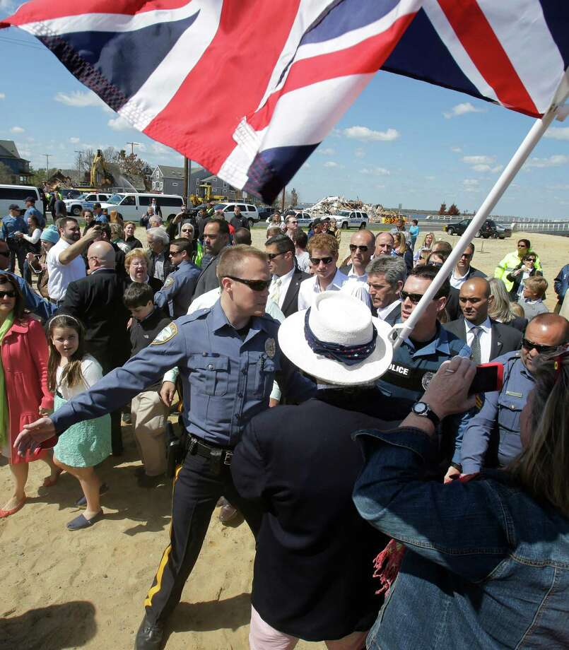 Britain's Prince Harry, center, walks with a crowd as a man waves a British flag during a visit to the area hit by Superstorm Sandy, Tuesday, May 14, 2013, in Seaside Heights, N.J.  Prince Harry began a tour  of New Jersey's storm-damaged coastline, inspecting dune construction, walking past destroyed homes and shaking hands with police and other emergency workers.  New Jersey sustained about $37 billion worth of damage from the storm. Photo: Mel Evans, AP / Pool AP