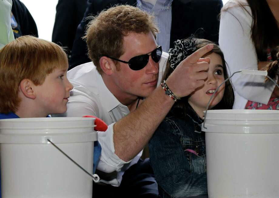 Michael Vanover, 7, left, looks on as Britain's Prince Harry helps Taylor Cirigliano, 11, right, pick a prize at a Ball Toss game on the boardwalk,  while visiting the area hit by Superstorm Sandy, Tuesday, May 14, 2013, in Seaside Heights, N.J.  Prince Harry began a tour  of New Jersey's storm-damaged coastline, inspecting dune construction, walking past destroyed homes and shaking hands with police and other emergency workers.  New Jersey sustained about $37 billion worth of damage from the storm. Photo: Mel Evans, AP / AP