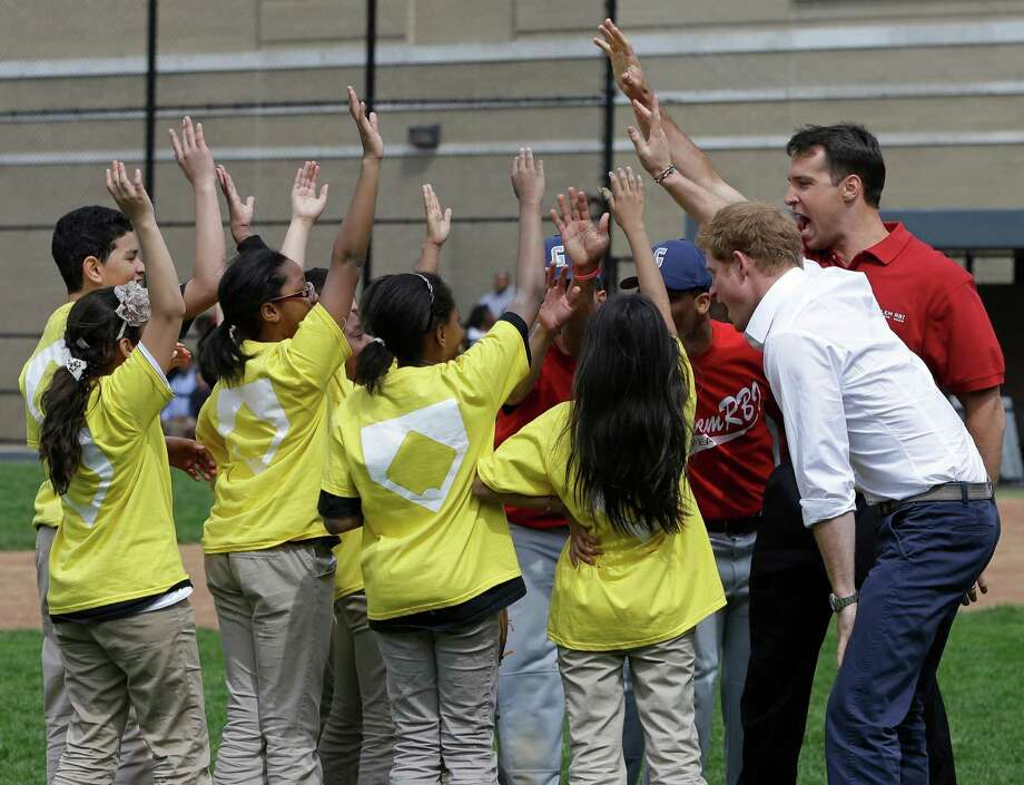 Britain's Prince Harry, second from right, in white shirt, and New York Yankees Mark Teixeira trade celebratory gestures with youngsters during a visit to the Harlem RBI  youth sports and baseball program in New York, Tuesday, May 14, 2013. Photo: Kathy Willens, AP / AP