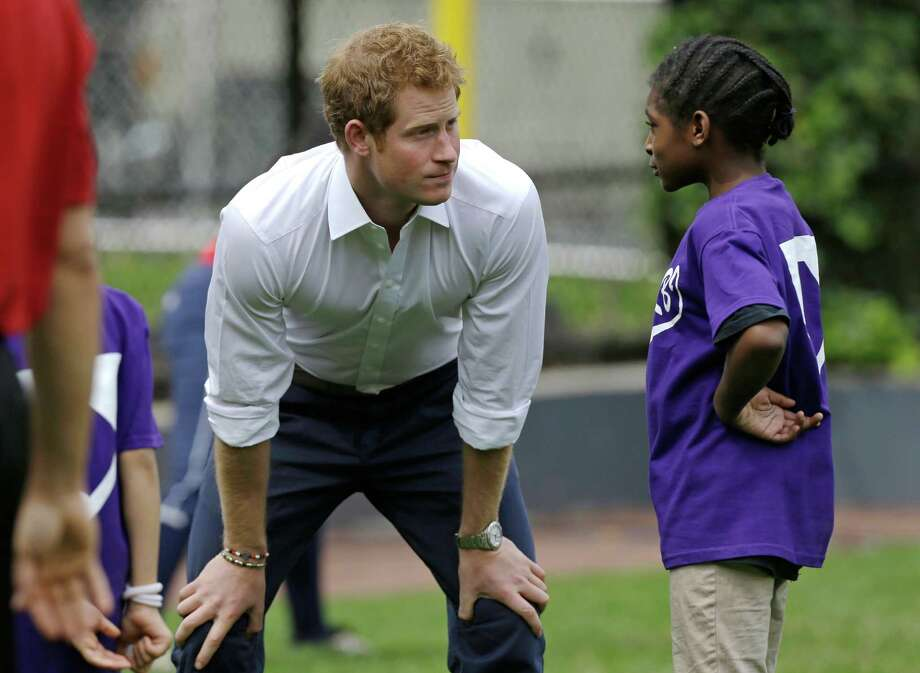 Britain's Prince Harry talks wtih a youngster during a visit to the Harlem RBI baseball and school program and to launch a partnership between himself, the program and the Royal Foundation of the Duke and Duchess of Cambridge in New York, Tuesday, May 14, 2013. Photo: Kathy Willens, AP / AP
