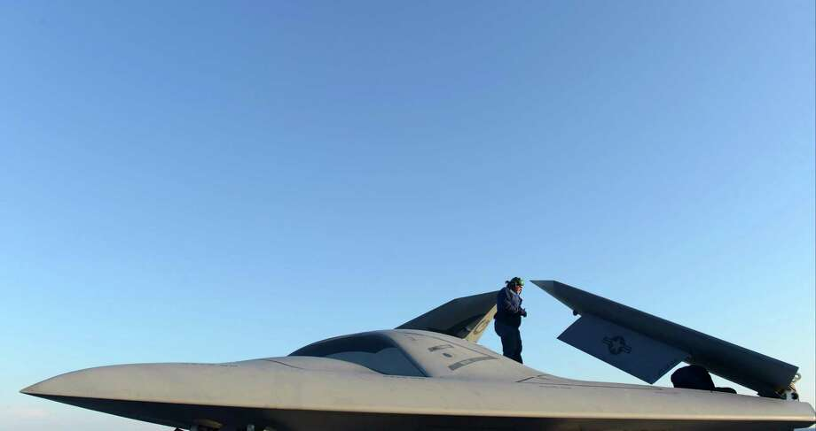 ATLANTIC OCEAN - MAY 14:  In this handout released by the U.S. Navy, Northrop Grumman personnel conduct pre-operational tests on an X-47B Unmanned Combat Air System (UCAS) demonstrator on the flight deck of the aircraft carrier USS George H.W. Bush (CVN 77) May 14, 2013 in the Atlantic Ocean. George H.W. Bush is scheduled to be the first aircraft carrier to catapult-launch an unmanned aircraft from its flight deck. The Navy plans to have unmanned aircraft on each of its carriers to be used for surveillance and be armed and used in combat roles. Photo: U.S. Navy, Getty Images / 2013 U.S. Navy