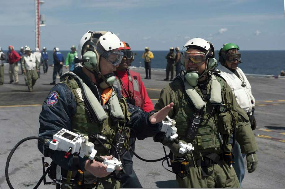 ATLANTIC OCEAN - MAY 14:  In this handout released by the U.S. Navy, Dave Lorenz, left, and Bruce McFadden, deck operators for Northrop Grumman, discuss the launch of an X-47B Unmanned Combat Air System (UCAS) demonstrator on the flight deck of the aircraft carrier USS George H.W. Bush (CVN 77) May 14, 2013 in the Atlantic Ocean. Lorenz and McFadden operated the X-47B as it taxied from the aircraft elevator to the catapult. George H.W. Bush is scheduled to be the first aircraft carrier to catapult-launch an unmanned aircraft from its flight deck. The Navy plans to have unmanned aircraft on each of its carriers to be used for surveillance and be armed and used in combat roles. Photo: U.S. Navy, Getty Images / 2013 U.S. Navy