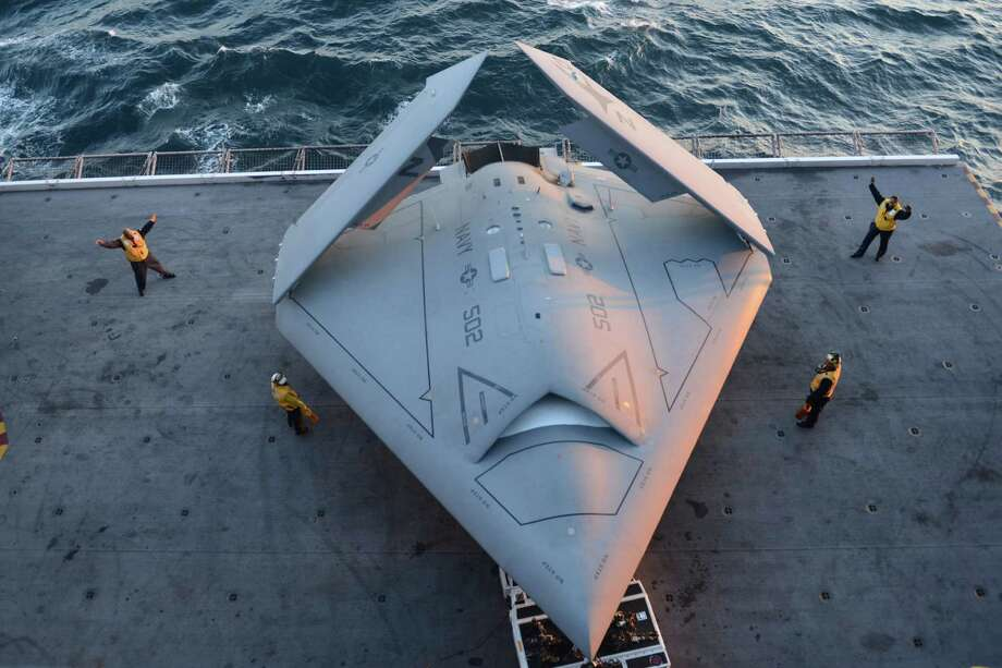 This image provided by the US navy shows sailors moving an X-47B Unmanned Combat Air System (UCAS) demonstrator onto an aircraft elevator aboard the aircraft carrier USS George H.W. Bush  Tuesday, May 14, 2013. The drone was launched off the George H.W. Bush to be the first aircraft carrier to catapult launch an unmanned aircraft from its flight deck. Photo: Timothy Walter, AP / US NAVY