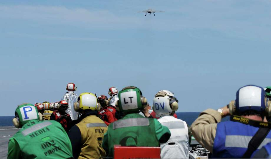Sailors and guests watch as a Navy X-47B drone is launched off the nuclear powered aircraft carrier USS George H. W. Bush off the coast of Virginia, Tuesday, May 14, 2013.   It was the Navy's first test flight of the unmanned aircraft off a carrier. Photo: Steve Helber, AP / AP