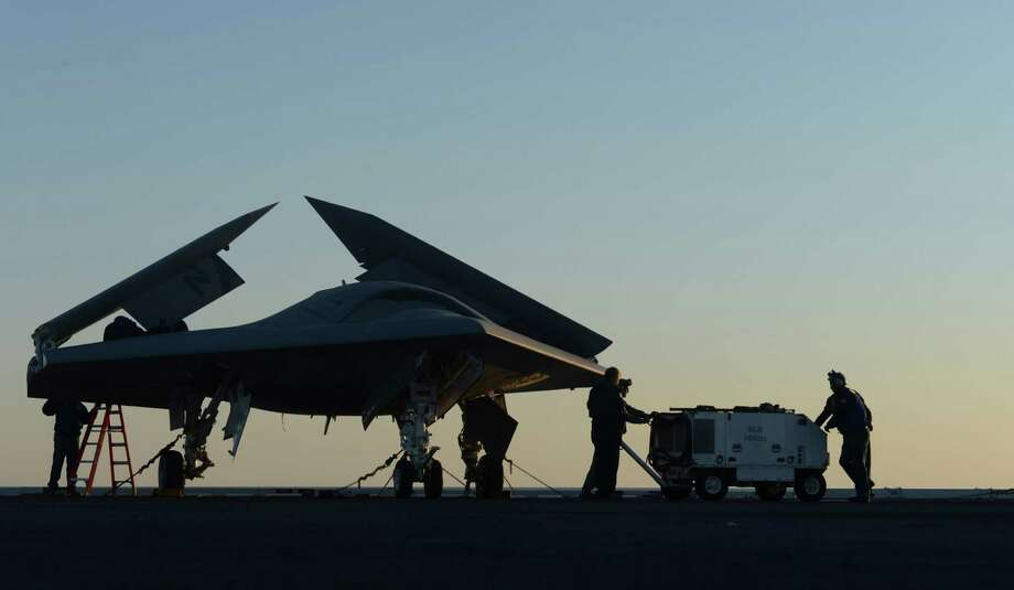 An image provided by the US Navy shows sailors working on an X-47B Unmanned Combat Air System (UCAS) at dawn aboard the aircraft carrier USS George H.W. Bush  Tuesday, May 14, 2013. The drone was launched off the George H.W. Bush to be the first aircraft carrier to catapult launch an unmanned aircraft from its flight deck. Photo: Timothy Walter, AP / US NAVY
