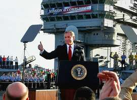 "** FILE ** President Bush flashes a ""thumbs-up"" after declaring the end of major combat in Iraq as he speaks aboard the aircraft carrier USS Abraham Lincoln off the California coast, in this May 1, 2003 file photo. One year later Bush and his advisers are struggling with the complexities of escalating violence in Iraq and a burgeoning American death toll. ""Mission accomplished"" is looking more like mission impossible. (AP Photo/J. Scott Applewhite, File)"