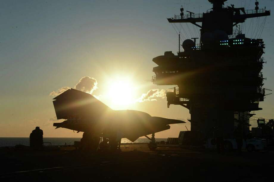 An image provided by the US Navy shows sailors moving an X-47B Unmanned Combat Air System (UCAS) at dawn aboard the aircraft carrier USS George H.W. Bush Tuesday, May 14, 2013. The drone was launched off the George H.W. Bush to be the first aircraft carrier to catapult launch an unmanned aircraft from its flight deck. Photo: Timothy Walter, AP / US NAVY
