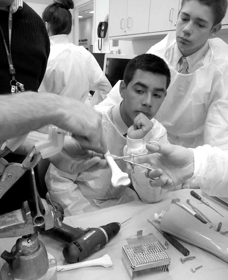 "Greenwich Country Day School students Danny Roca and Wills Danielson get some hands-on experience with actual surgical equipment  during the ""Doctor for A Day"" program at the Orthopaedic Foundation for Active Lifestyles in Greenwich. Photo: Contributed Photo"