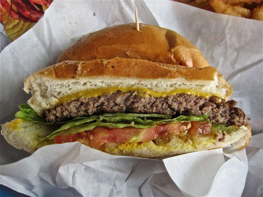 The cheeseburger at Carlos Beer Garden & Barber Shop lacked the ooze factor to make a passing grade. Photo: Alison Cook