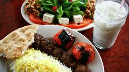The Sultani, a skewer of beef Kubideh and a skewer of beef Barg along with white rice, the Special Herb Plate and a cup of Doogh, a yogurt drink, at Kasra Persian Grill Tuesday, June 15, 2010, in Houston.   ( Michael Paulsen / Houston Chronicle )