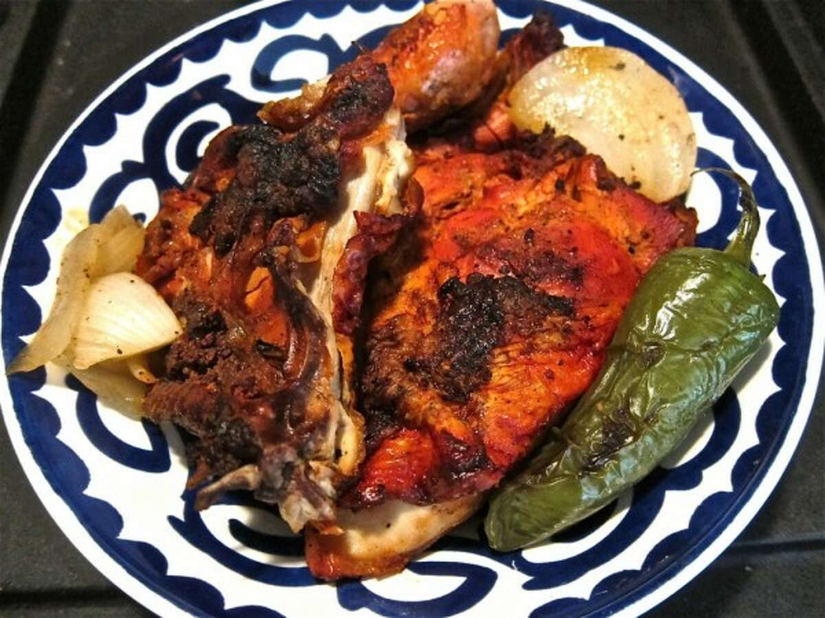 Half mesquite-grilled chicken from Karanchos Seabrook, with onion and chile toreado.