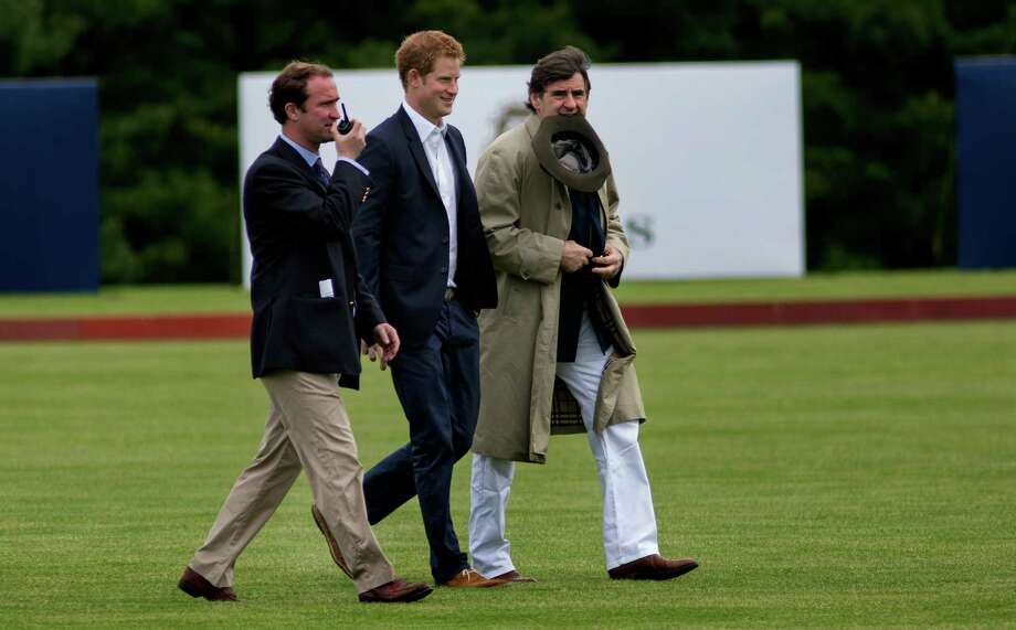 Britain's Prince Harry walks across the polo field before the Sentebale Royal Salute Polo Cup charity match in Greenwich, Conn., Wednesday, 15, 2103. Right is Peter Brant, founder of the Greenwich Polo Club. (AP Photo/Craig Ruttle) Photo: Craig Ruttle, AP / Associated Press