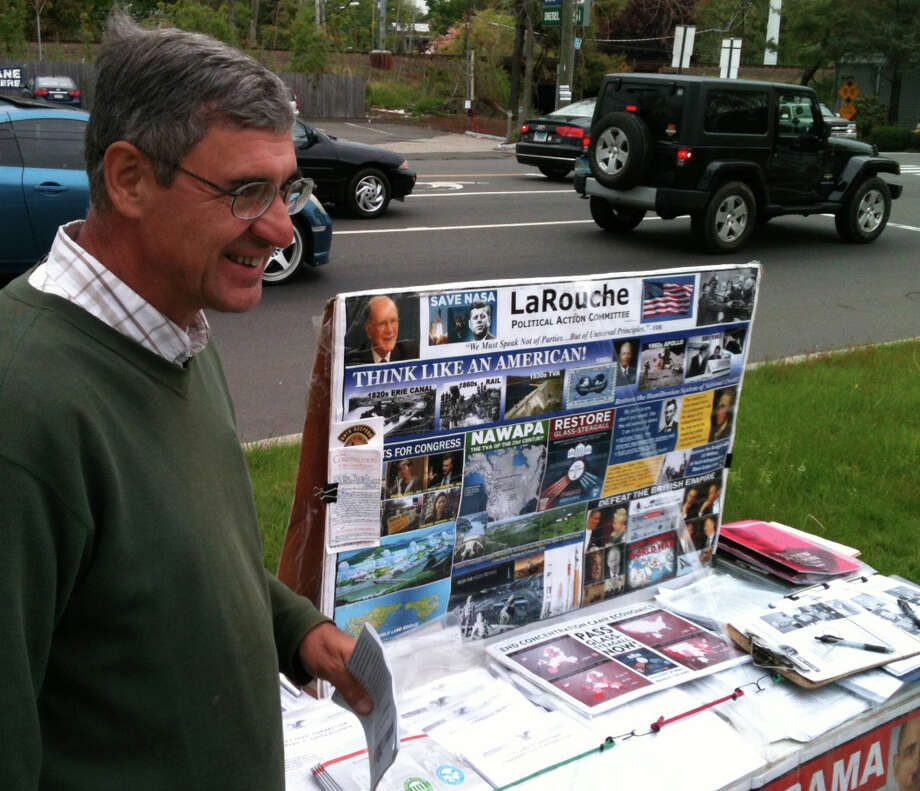 John Scialdone, a member of LaRouche PAC, stands by a table set up Wednesday by the Post Road with materials supporting the group's call for President Obama to be impeached. FAIRFIELD CITIZEN, CT 5/15/13 Photo: Andrew Brophy / Fairfield Citizen contributed