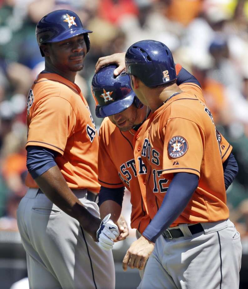 J.D. Martinez, center, is congratulated by Carlos Pena, right, and Chris Carter after hitting a three-run home run off Tigers pitcher Max Scherzer during the fourth inning.