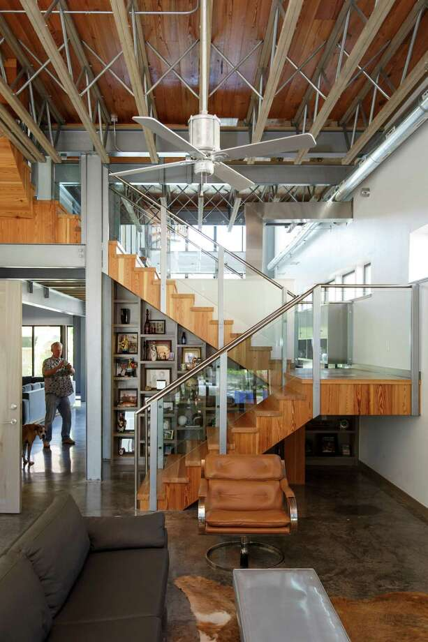 A meticulously crafted pine staircase is the only structure that divides the open first-floor space. Photo: Michael Paulsen, Staff / © 2013 Houston Chronicle