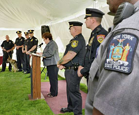 CAP COM president and CEO Paula Stopera, center, hosts 8 police departments, Colonie Police K-9 Vader, students and CAP COM staff to a celebration of Police Week at the CapCom Federal Credit Union in Colonie, NY Wednesday May 15, 2013.  (John Carl D'Annibale / Times Union) Photo: John Carl D'Annibale / 00022440A