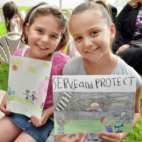 Maci Dahlberg,9, left, and Kyla Zeilman, 8, both of Colonie with winning artwork as CAP COM hosts 8 police departments, Colonie Police K-9 Vader, students and CAP COM staff to a celebration of Police Week at the CapCom Federal Credit Union in Colonie, NY Wednesday May 15, 2013. Students from ten local schools created illustrations to show what it means to be a police officer.  (John Carl D'Annibale / Times Union) Photo: John Carl D'Annibale / 00022440A