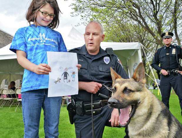 Margaret Webber, 8, of Troy shows her drawing of a police officer and K9 partner to Colonie police officer Jerry Shaw and Colonie Police K-9 Vader during a Police Week celebration at the CapCom Federal Credit Union in Colonie, NY Wednesday May 15, 2013. Students from ten local schools created illustrations to show what it means to be a police officer.  (John Carl D'Annibale / Times Union) Photo: John Carl D'Annibale / 00022440A