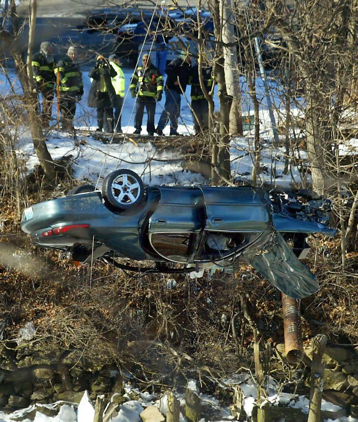 Bridgeport firefighters watch as a car is lifted from the Pequonnock River in Bridgeport. Firefighters pulled a male from the vehicle after it was discovered in the Pequonnock River near River Street and Lindley. Sunday, Jan. 10, 2010.