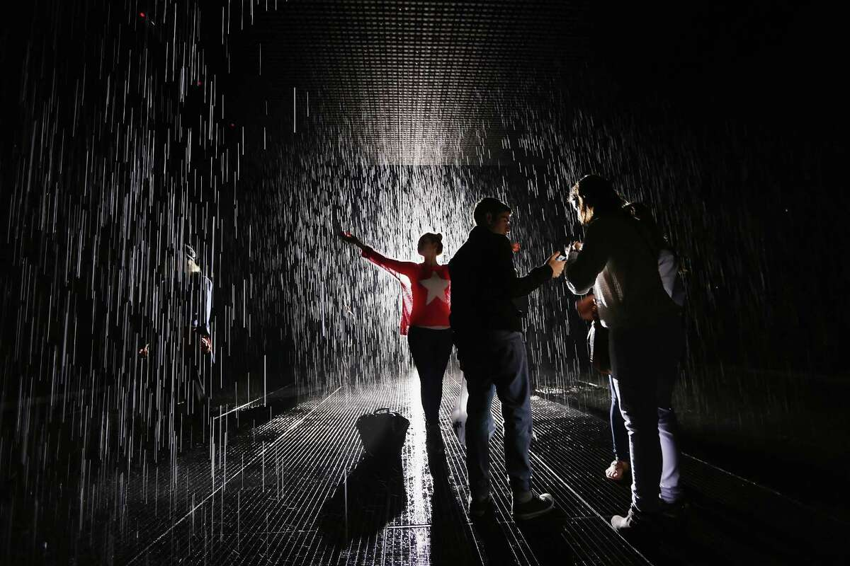 Visitors gather in the new 'Rain Room' installation at the Moma.