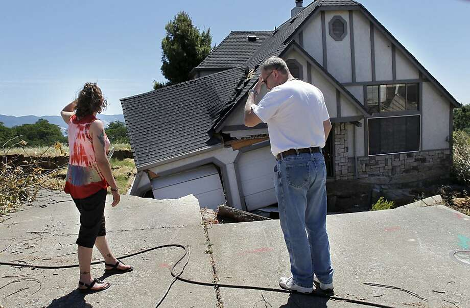 Robin and Scott Spivey look at their home, which has been destroyed by the landslide. The ground began slipping in March, and several homes in the Lakeside Heights neighborhood have been swallowed up. Photo: Michael Macor, The Chronicle