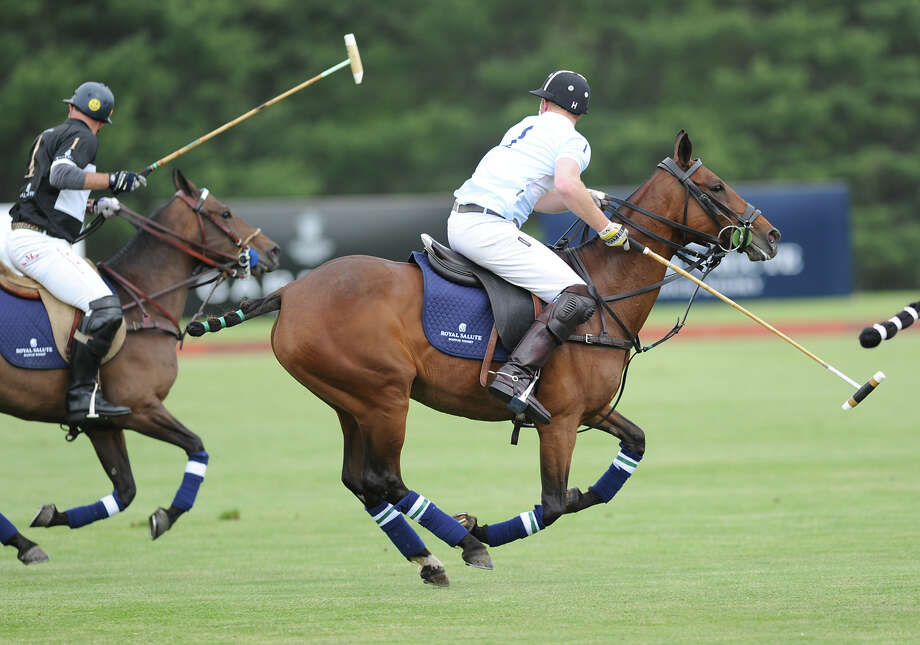 At right, Prince Harry in action during the Sentebale Royal Salute Polo Cup match at the Greenwich Polo Club, Wednesday, May 15, 2013. The polo match was played to raise funds for Sentebale, a charity Prince Harry co-founded in 2006 in memory of his late mother, Princess Diana. Photo: Bob Luckey / Greenwich Time