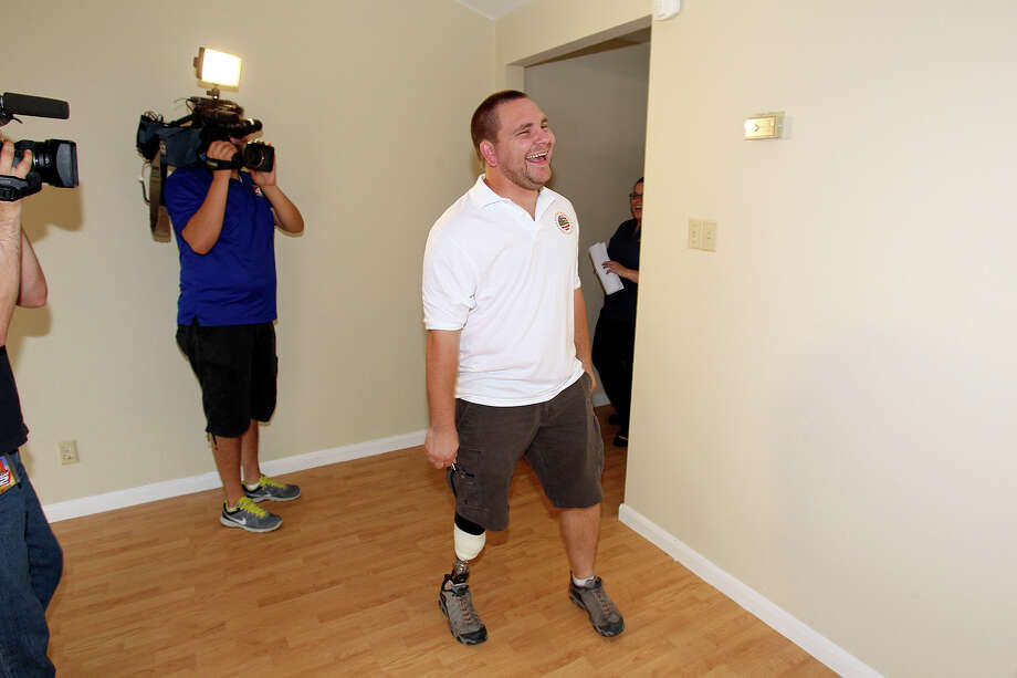 James Ford, who lost his lower right leg in Afghanistan in 2007, sees his living room for the first time after he is presented the keys to a home donated by Bank Of America  on  May 15, 2013. Photo: TOM REEL