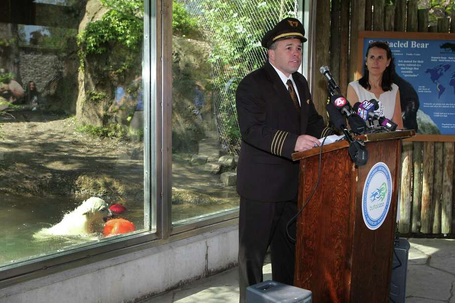 UPS Pilot Captain Jon Burrows speaks at a news conference that was held, Wednesday, May 15, 2013 in front of the exhibit holding the polar bear cub, Luna,  to announce the arrival of Kali, an orphaned cub found in Alaska. On right is Buffalo Zoo President, Donna Fernandez. The 65 pound male polar bear was shipped via UPS from the Alaska Zoo.  He was not yet available for viewing and will be introduced to Luna in a few weeks. Photo: Sharon Cantillon, Associated Press / The Buffalo News