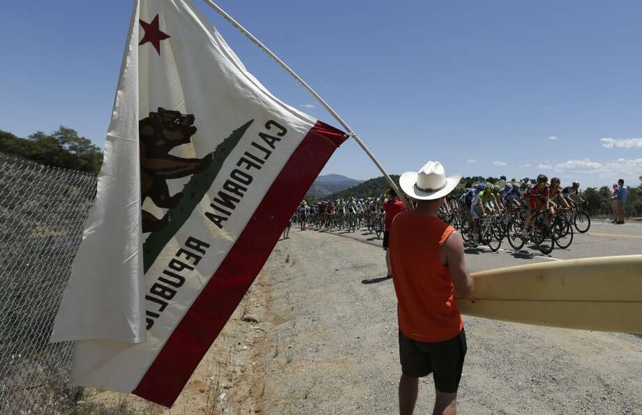 A man holds a Californian flag and a surfboard as the peloton passes during the first stage of the Tour of California cycling race over a 102.6 mile (165.12 kilometers) loop  Sunday, May 12, 2013, starting and finishing in Escondido, Calif.