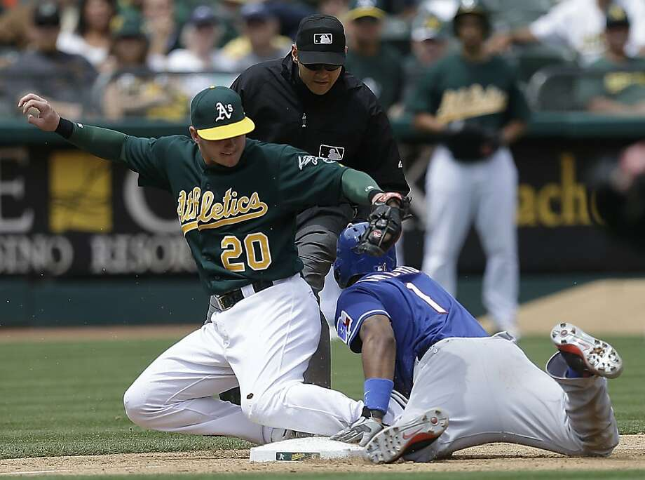 Texas Rangers' Elvis Andrus, right, slides beneath the tag of Oakland Athletics third baseman Josh Donaldson (20) to safely steal third base during the fifth inning of a baseball game Wednesday, May 15, 2013, in Oakland, Calif. (AP Photo/Ben Margot) Photo: Ben Margot, Associated Press