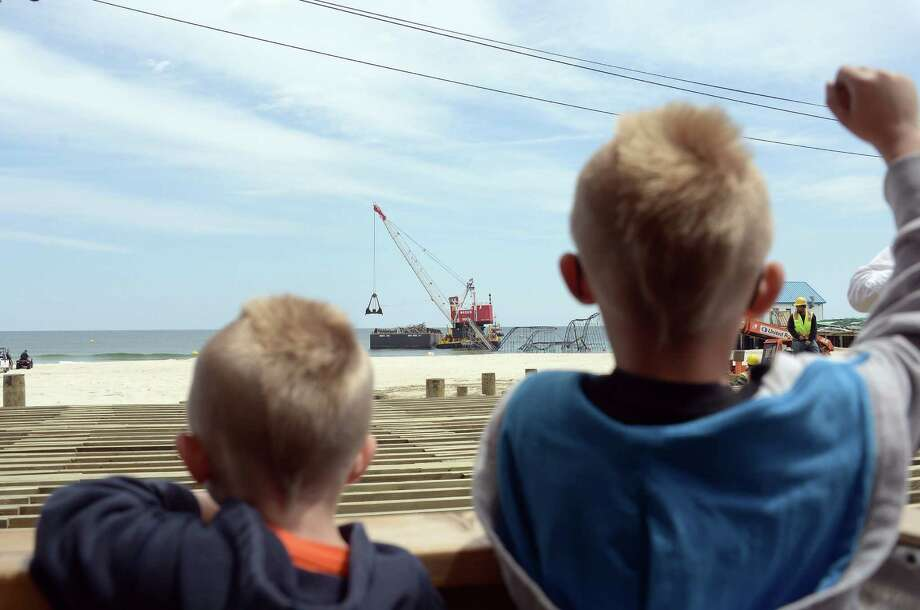 Two young boys watch a crane demolish the JetStar roller coaster that has been in the ocean for six months after the Casino Pier it sat on collapsed when Superstorm Sandy hit, May 14, 2013 in Seaside Heights, New Jersey. Photo: Michael Loccisano, Getty Images / 2013 Getty Images