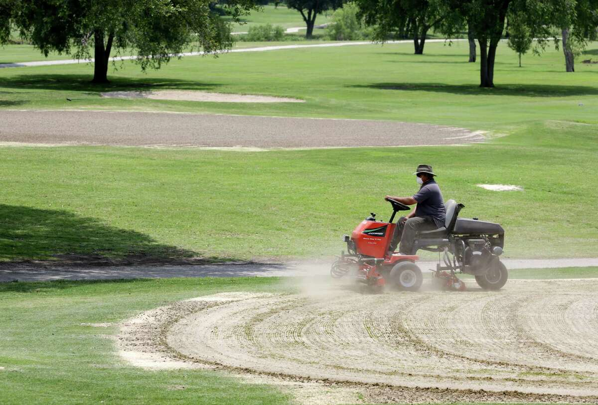 Dean Hiatt uses a vertical cutting machine on the practice putting green at Olmos Golf Course on Tuesday May 14, 2013, preparing them for the hot dry weather to come.