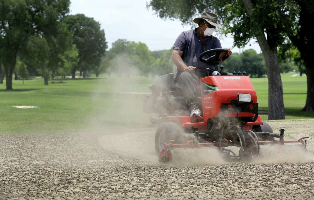 Dean Hiatt uses a vertical cutting machine on the practice putting green at Olmos Golf Course on Tuesday May 14, 2013, preparing the greens for the hot dry weather to come.