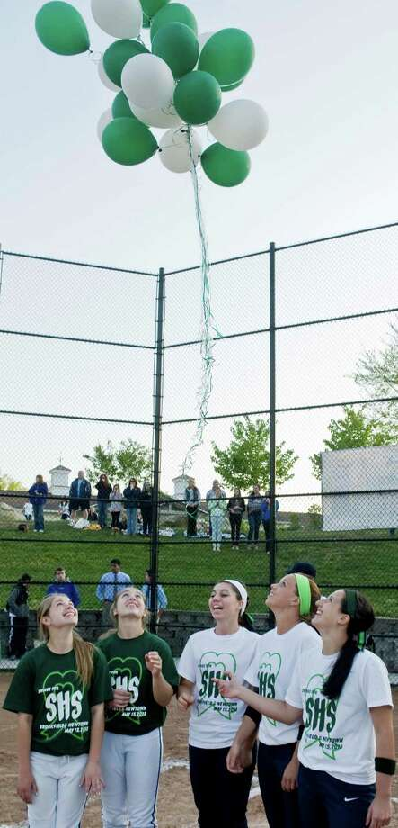 Newtown High School seniors Courtney Escoda and Jessica Gibbons, left, stand with Brookfield High School seniors Ashley Lamparelli, Felicia Lennon and Danielle DeMarco as they release balloons to commemorate the first annual Sandy Hook Memorial softball game held at Treadwell Park in Newtown. Wednesday, May 15, 2013 Photo: Scott Mullin / The News-Times Freelance