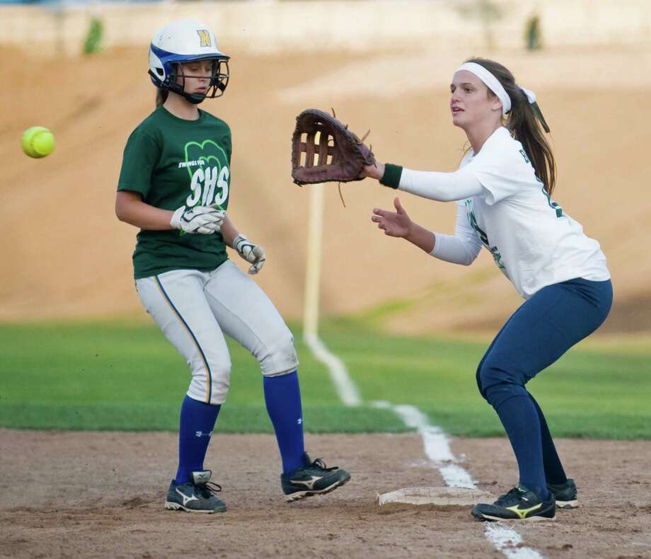 Newtown High School runner Mikayla Kuligowski gets back to the bag as  Brookfield High School first baseman Katie Layman takes a pick-off throw during the Sandy Hook Memorial softball game played at Treadwell Park in Newtown. Wednesday, May 15, 2013 Photo: Scott Mullin