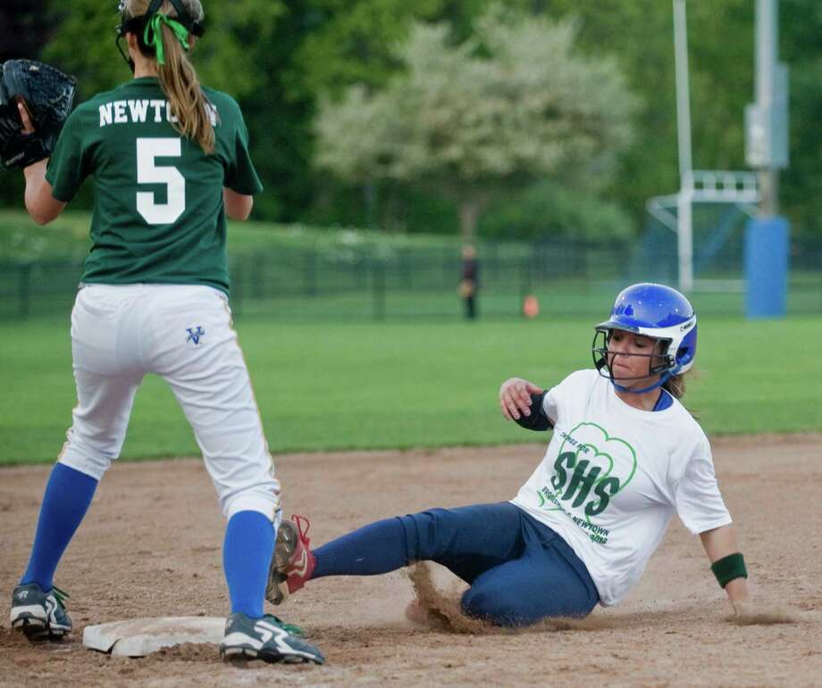 Newtown High School third baseman Kayla O'Grady waits for the throw as Brookfield High School runner Felicia Lennon slides into the bag during the Sandy Hook Memorial softball game played at Treadwell Park in Newtown. Wednesday, May 15, 2013 Photo: Scott Mullin / The News-Times Freelance
