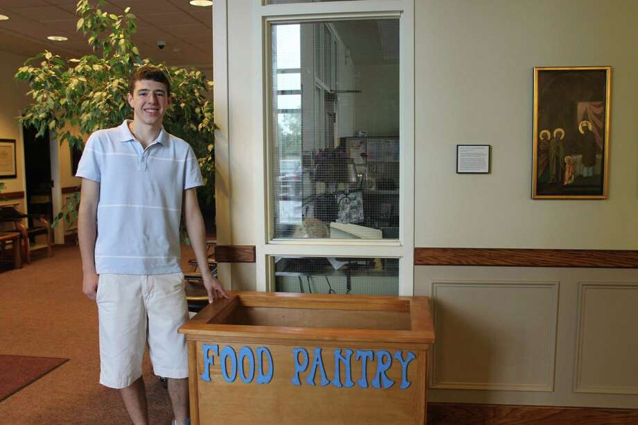 GOYA youth group president Alex Sokaris poses in front of the food collection box at St. Sophia Greek Orthodox Church in Albany. (Jennifer Patterson/Times Union)