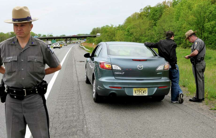 Troop G Public Information Officer Mark Cepiel, left, ensures motorists move over as Trooper Joseph Germano, right, tickets a Nebraska man for distracted driving on Wednesday, May 15, 2013, on Interstate 87 in Latham, N.Y. The out-of-town man was using a navigational feature on his cell phone. (Cindy Schultz / Times Union) Photo: Cindy Schultz / 00022320A