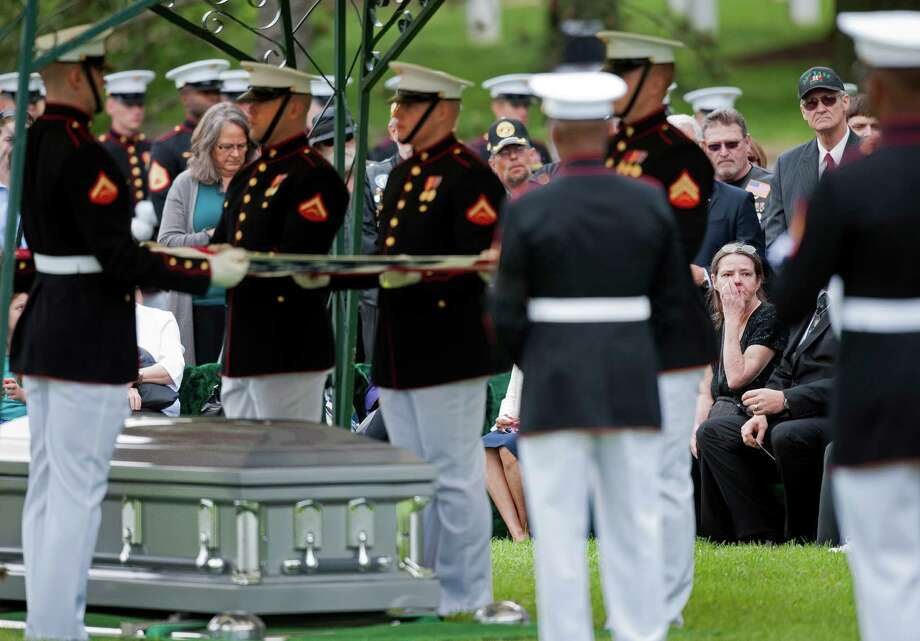 A family member of one of the 13 servicemen from the Vietnam War touches her face during the burial, in one casket, of the men at Arlington National Cemetery in Arlington, Va., Wednesday, May 15, 2013. (AP Photo/Cliff Owen) Photo: Cliff Owen, Associated Press / FR170079 AP