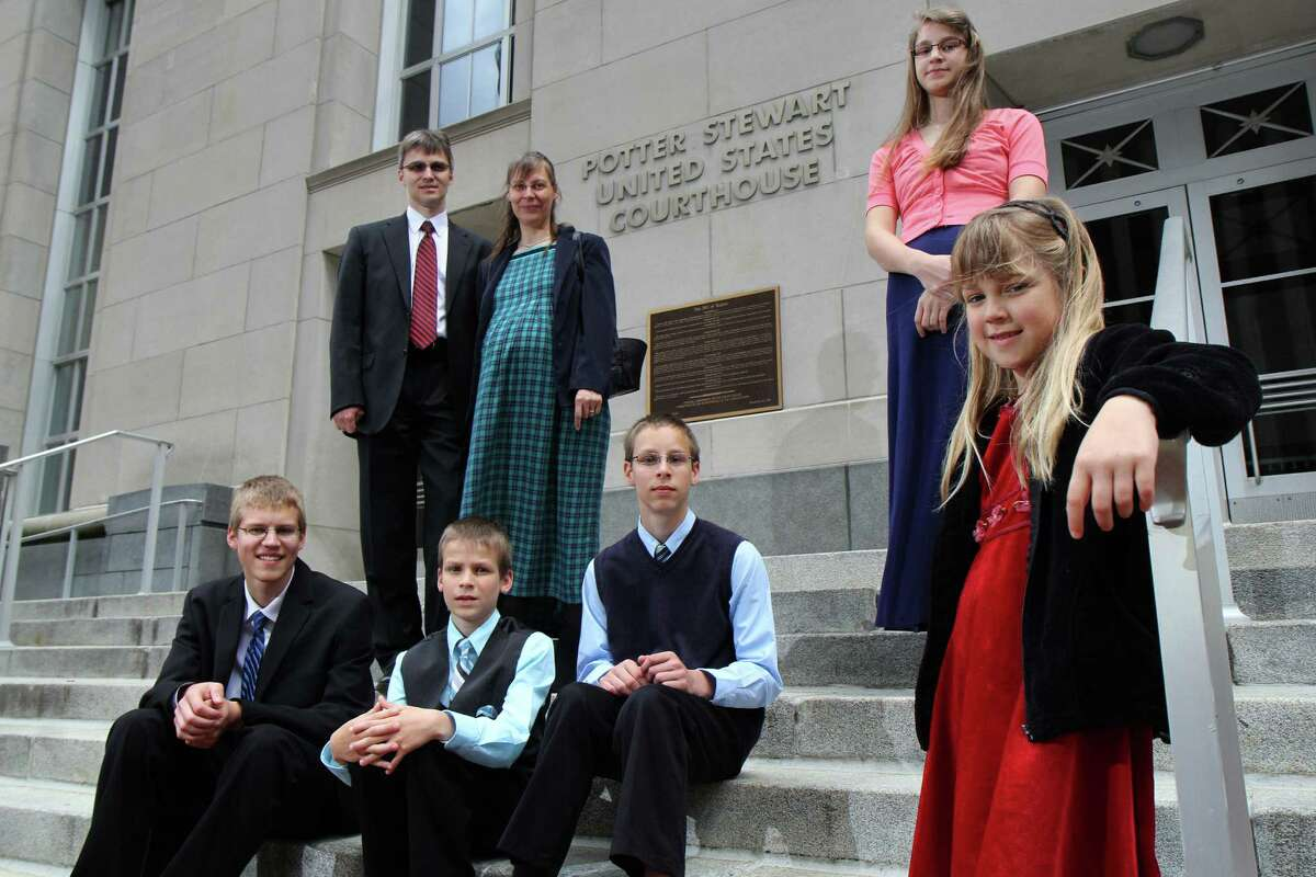 Uwe and mother Hannolure Romeike with their children, from left, Daniel, 16, Joshua, 13, Christian, 11, Lydia, 15 and Damaris, 7, outside the federal courthouse in Cincinnati Tuesday.
