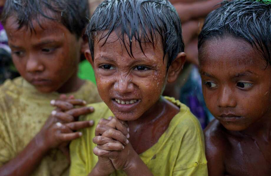 Internally displaced Rohingya boys shiver in rain in a makeshift camp for Rohingya people in Sittwe, northwestern Rakhine State, Myanmar, ahead of the arrival of Cyclone Mahasen expected later this week, Tuesday, May 14, 2013. The U.N. said they cyclone could swamp makeshift housing camps sheltering tens of thousands of Rohingya.  Myanmar state television reported Monday that 5,158 people were relocated from low-lying camps in Rakhine state to safer shelters. But far more people are considered vulnerable. (AP Photo/Gemunu Amarasinghe) Photo: Gemunu Amarasinghe, STF / AP