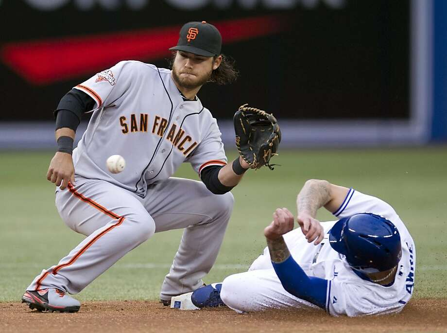 Toronto Blue Jays' Brett Lawrie, right, slides safely into second base as San Francisco Giants' Brandon Crawford looks toward the ball during first-inning AL baseball game action in Toronto, Wednesday, May 15, 2013.  (AP Photo/The Canadian Press, Frank Gunn) Photo: Frank Gunn, Associated Press