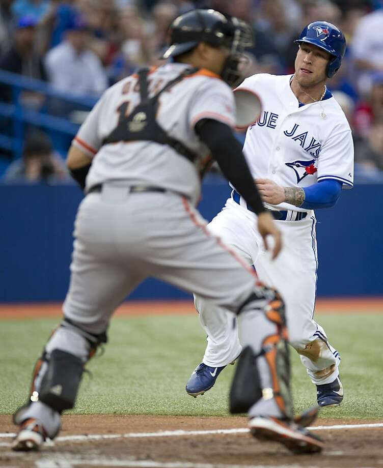 Toronto Blue Jays' Brett Lawrie, right, slides home on an Edwin Encarnacion single as San Francisco Giants' Guillermo Quiroz, left, looks for the ball during first-inning AL baseball game action in Toronto, Wednesday, May 15, 2013.  (AP Photo/The Canadian Press, Frank Gunn) Photo: Frank Gunn, Associated Press