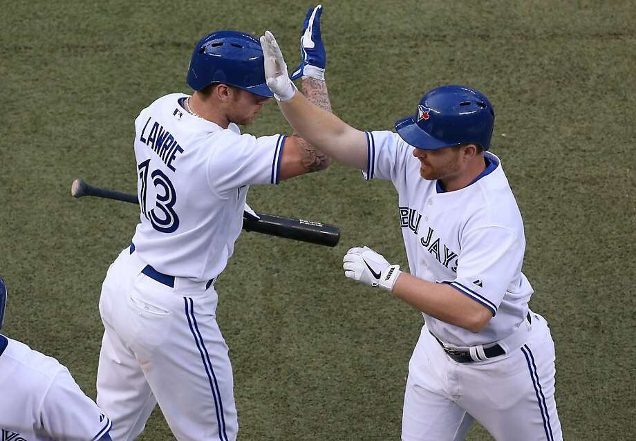 TORONTO, CANADA - MAY 15: Adam Lind #26 of the Toronto Blue Jays is congratulated by Brett Lawrie #13 after hitting a 2-run home run in the first inning during MLB game action against the San Francisco Giants on May 15, 2013 at Rogers Centre in Toronto, Ontario, Canada. (Photo by Tom Szczerbowski/Getty Images) Photo: Tom Szczerbowski, Getty Images