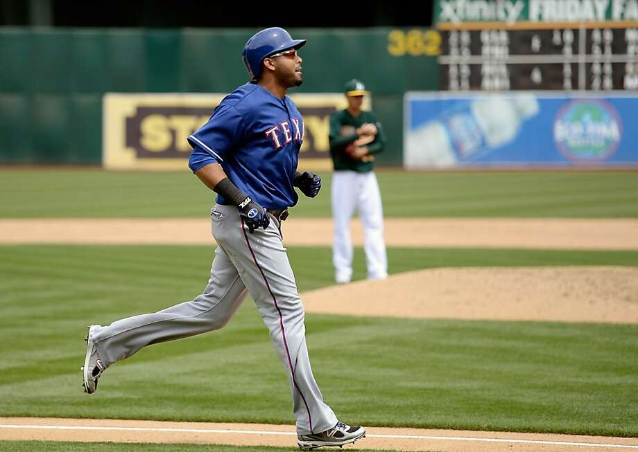OAKLAND, CA - MAY 15:  Nelson Cruz #17 of the Texas Rangers trots around the bases after hitting a three-run homer as pitcher Jesse Chavez #60 of the Oakland Athletics looks on in the fifth inning at O.co Coliseum on May 15, 2013 in Oakland, California.  (Photo by Thearon W. Henderson/Getty Images) Photo: Thearon W. Henderson, Getty Images