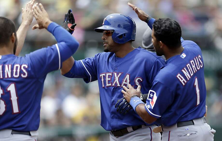 Texas Rangers' Nelson Cruz, center, celebrates with Elvis Andrus (1) and Robinson Chirinos, left, after hitting a three-run home run off Oakland Athletics' Jesse Chavez in the fifth inning of a baseball game on Wednesday, May 15, 2013, in Oakland, Calif. (AP Photo/Ben Margot) Photo: Ben Margot, Associated Press