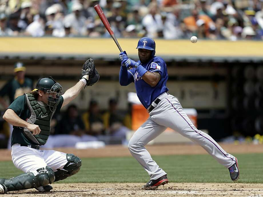 Texas Rangers' Elvis Andrus, right, is hit by a pitch thrown by Oakland Athletics' Dan Straily in the third inning of a baseball game on Wednesday, May 15, 2013, in Oakland, Calif. (AP Photo/Ben Margot) Photo: Ben Margot, Associated Press