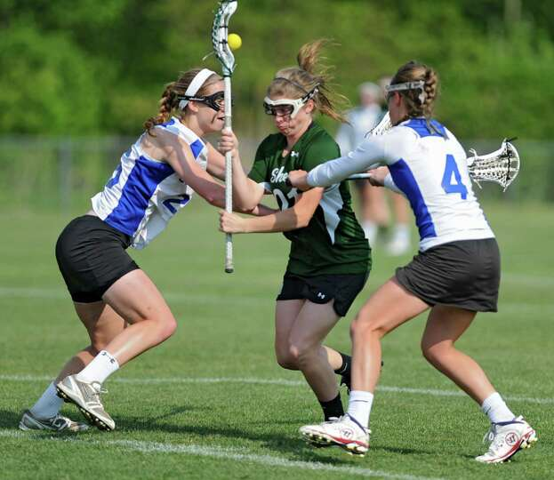 Shenendehowa's Kelly Wall, center, is defended by Shaker's Eva Torcello, left, and Sarah Cheney duri