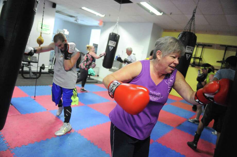 Peg Willi, right, of Charleston joins other boxing aficionados hitting the heavy bags for an hour straight with no breaks to raise money for St. Jude's Children's Hospital at Schenectady Youth Boxing on Wednesday May 15 2013 in Schenectady, N.Y. (Michael P. Farrell/Times Union) Photo: Michael P. Farrell